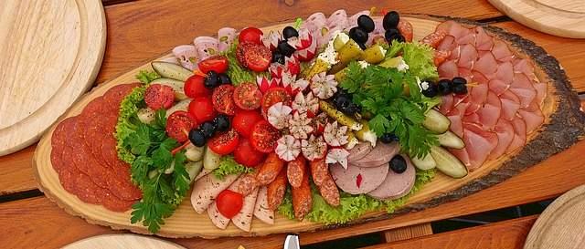 magnifique plateau de charcuterie sur un rondin de bois avec des légumes et des olives faire un beau plateau de charcuterie