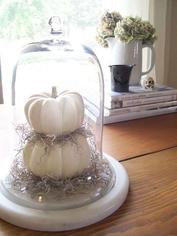 Des citrouilles en blanc superposées dans une dôme en verre pour une touche d'élégance